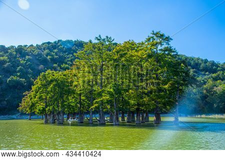 Sukko Cypress Lake With Cypress Trees Growing In The Water, Surrounded By Forests And Mountains.