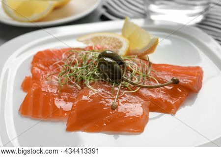 Salmon Carpaccio With Capers, Microgreens And Lemon On Plate, Closeup