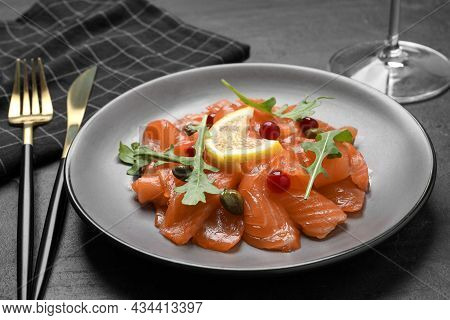 Salmon Carpaccio With Capers, Cranberries, Arugula And Lemon Served On Black Table
