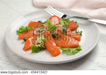 Salmon Carpaccio With Capers, Lettuce, Microgreens And Onion On White Wooden Table, Closeup