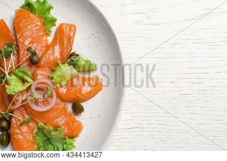 Salmon Carpaccio With Capers, Lettuce, Microgreens And Onion On White Wooden Table, Top View. Space