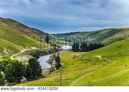 The road runs along the river. The magnificent landscape of New Zealand. The hills were overgrown with yellowed grass. The concept of active, environmental and photo tourism
