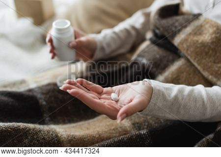 Partial View Of Diseased Woman With Pill On Open Palm, Blurred Background