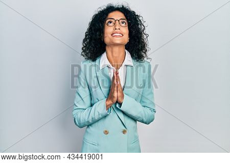 Young latin girl wearing business clothes and glasses begging and praying with hands together with hope expression on face very emotional and worried. begging.
