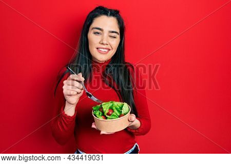 Young hispanic girl eating salad winking looking at the camera with sexy expression, cheerful and happy face.