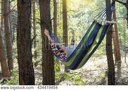 Freelance And Working At Nature. Woman Freelancer Works At Notebook While Lying On The Hammock In Th