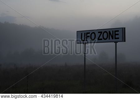 Signpost With Text Ufo Zone On The Background Of The Evening Foggy Forest.