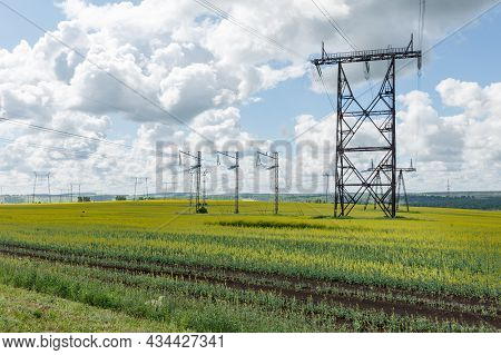 Electricity Pylon. High Voltage Power Transmission Tower. Power Lines In The Field.