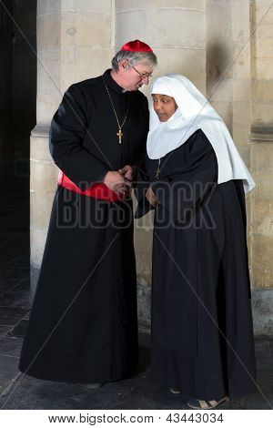 Nun and Cardinal talking against a background of an old pillar in a medieval church