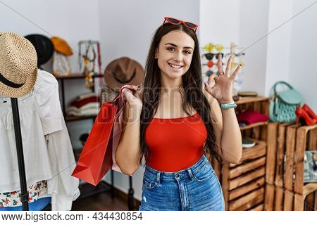 Young brunette woman holding shopping bags at retail shop smiling positive doing ok sign with hand and fingers. successful expression.