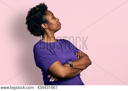 African american woman with afro hair wearing casual purple t shirt looking to the side with arms crossed convinced and confident