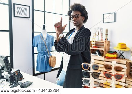 African young woman working as manager at retail boutique holding symbolic gun with hand gesture, playing killing shooting weapons, angry face