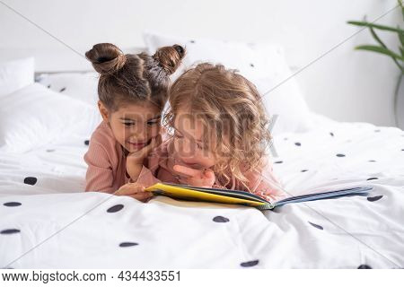 Two Diverse Kids Girl Sisters Friends In Pajamas Reading Book Lying On White Bedding On Bed At Home