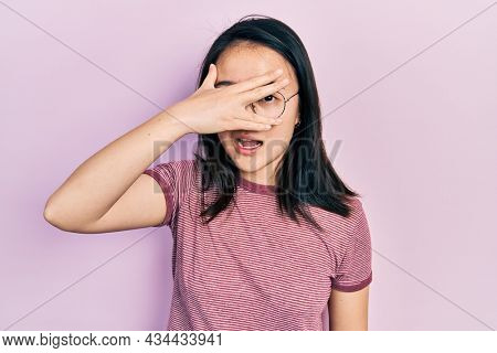 Young chinese girl wearing casual clothes and glasses peeking in shock covering face and eyes with hand, looking through fingers with embarrassed expression.