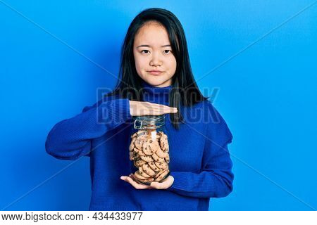 Young chinese girl holding jar of chocolate chips cookies skeptic and nervous, frowning upset because of problem. negative person.
