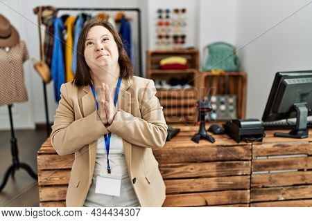 Young down syndrome woman working as manager at retail boutique begging and praying with hands together with hope expression on face very emotional and worried. begging.