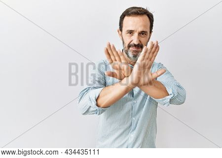 Middle age hispanic man with beard standing over isolated background rejection expression crossing arms and palms doing negative sign, angry face