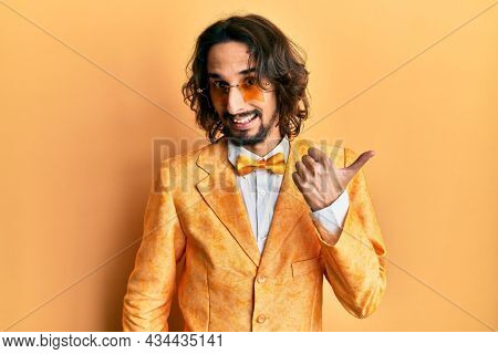 Young hispanic man wearing hipster elegant look smiling with happy face looking and pointing to the side with thumb up.