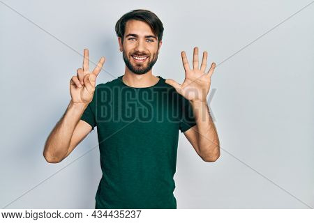 Young hispanic man wearing casual white tshirt showing and pointing up with fingers number seven while smiling confident and happy.