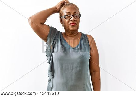 Mature hispanic woman wearing glasses standing over isolated background confuse and wondering about question. uncertain with doubt, thinking with hand on head. pensive concept.