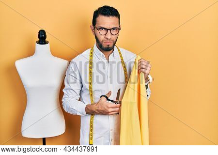 Hispanic man with beard dressmaker designer holding scissors and cloth skeptic and nervous, frowning upset because of problem. negative person.