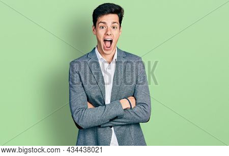 Young hispanic business man with arms crossed gesture celebrating crazy and amazed for success with open eyes screaming excited.