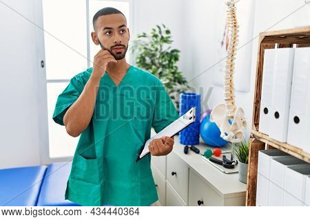 African american physiotherapist man working at pain recovery clinic with hand on chin thinking about question, pensive expression. smiling with thoughtful face. doubt concept.