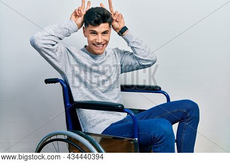Young hispanic man sitting on wheelchair posing funny and crazy with fingers on head as bunny ears, smiling cheerful