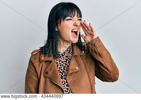 Young hispanic woman wearing casual leather jacket shouting and screaming loud to side with hand on mouth. communication concept.