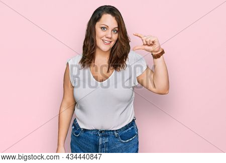 Young plus size woman wearing casual white t shirt smiling and confident gesturing with hand doing small size sign with fingers looking and the camera. measure concept.