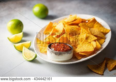 Single Oval Shaped White Bowl Of Yellow Corn Tortilla Nachos Chips With Salsa Sauce Over White Table