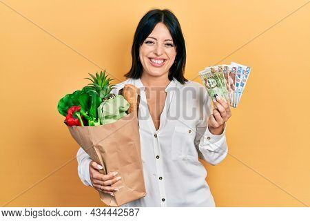 Young hispanic woman holding groceries bag and peruvian sol banknotes smiling and laughing hard out loud because funny crazy joke.