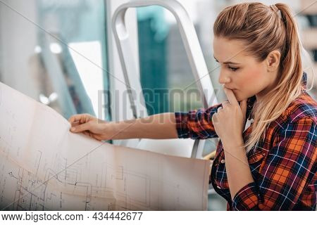 Portrait of a Serious Interior Architect. Woman Thinking about Apartment Design Plan. House Renovation.