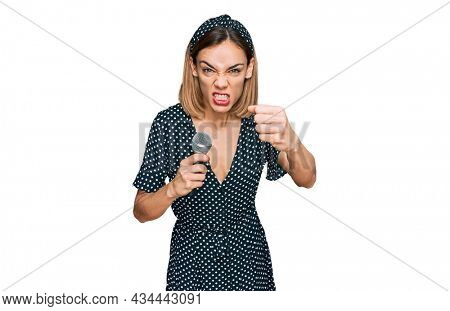 Young blonde girl singing song using microphone annoyed and frustrated shouting with anger, yelling crazy with anger and hand raised