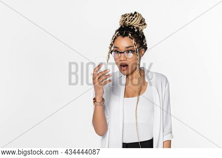 Astonished African American Businesswoman In Eyeglasses Looking At Mobile Phone Isolated On White