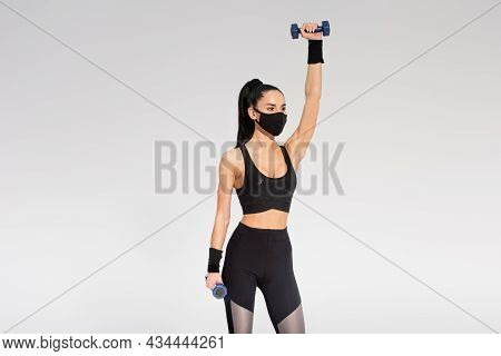 Sportswoman In Black Protective Mask Working Out With Dumbbells On Grey