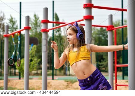 Side View Portrait Young Hipster Little Girl Wearing Singlet And Trendy Wireless Headphones On Sport