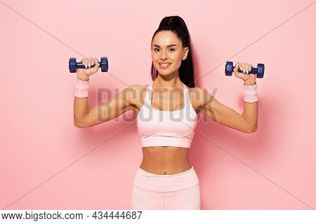 Joyful Young Sportswoman Exercising With Dumbbells On Pink