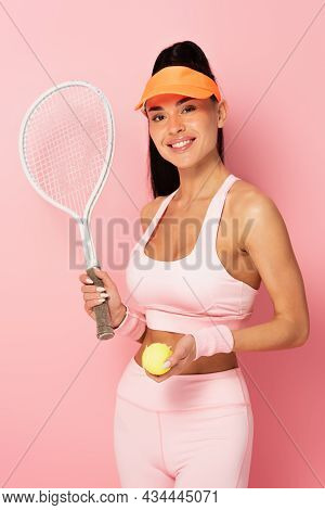 Positive Sportswoman In Tennis Cap Holding Tennis Racket And Ball On Pink