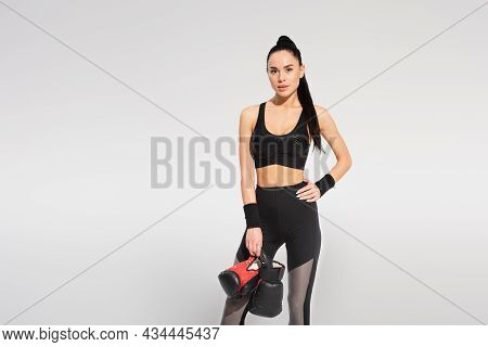Sportswoman Holding Boxing Gloves While Posing With Hand On Hip Isolated On Grey