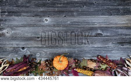 Bottom Border Real Whole Pumpkin, Corn, Acorns And Foliage Leaves On Weathered Wooden Planks For The