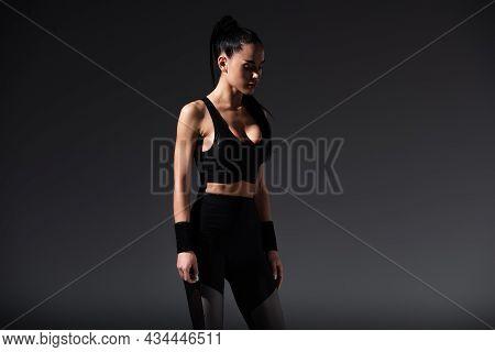 Young Sportswoman In Black Sportswear Standing On Dark Background