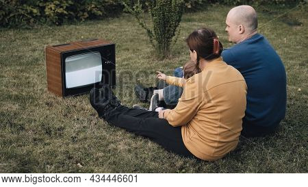 Family Of A Man, A Woman And Little Baby Are Sitting On The Grass And Watching An Old Retro Tv. The