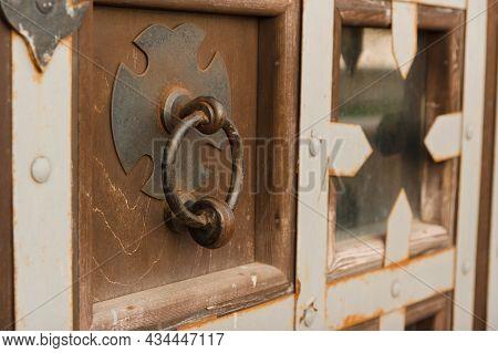 Antique Door Knocker In A Round Shape On A Wooden Door. Reconstruction Of An Antique Door Knocker