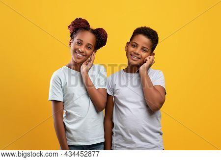 Cute African American Siblings Sharing Earphones, Listening To Music