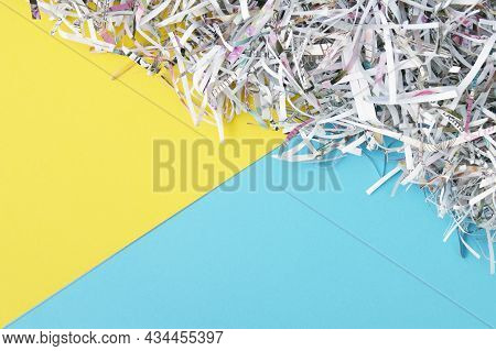 The Shredded Paper On Light Yellow And Blue Background.