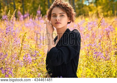 A Beautiful Young Woman With A Bouquet Of Lupine In Her Hand.soft Focus