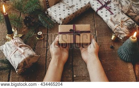 Christmas Rustic Gift. Hands Holding Stylish Christmas Gift Wrapped In Craft Paper On Rustic Wooden