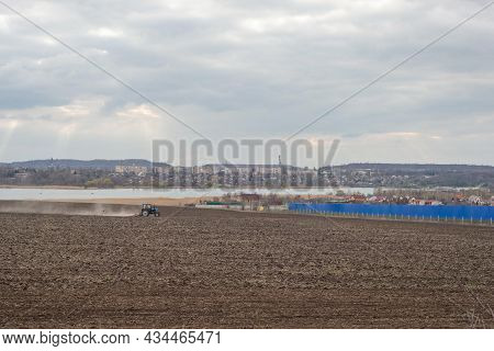 Plowed Field Against The Background Of Clouds And Sunbeams. Spring Cleaning Of The Land, Preparation