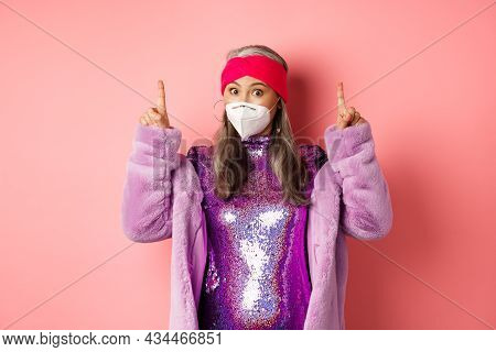 Covid And Fashion Concept. Fashionable Asian Woman In Glitter Dress And Face Mask, Pointing Fingers